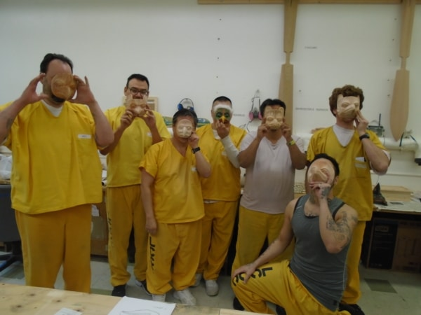 Lemon Creek Correctional Center incarcerated residents in the woodworking shop holding up their unfinished masks to their faces.