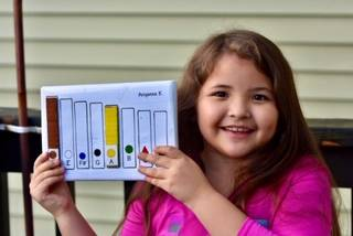 An elementry student holding up a xylophone made by inmates at Lemon Creek Correctional Centers in Juneau, Alaska