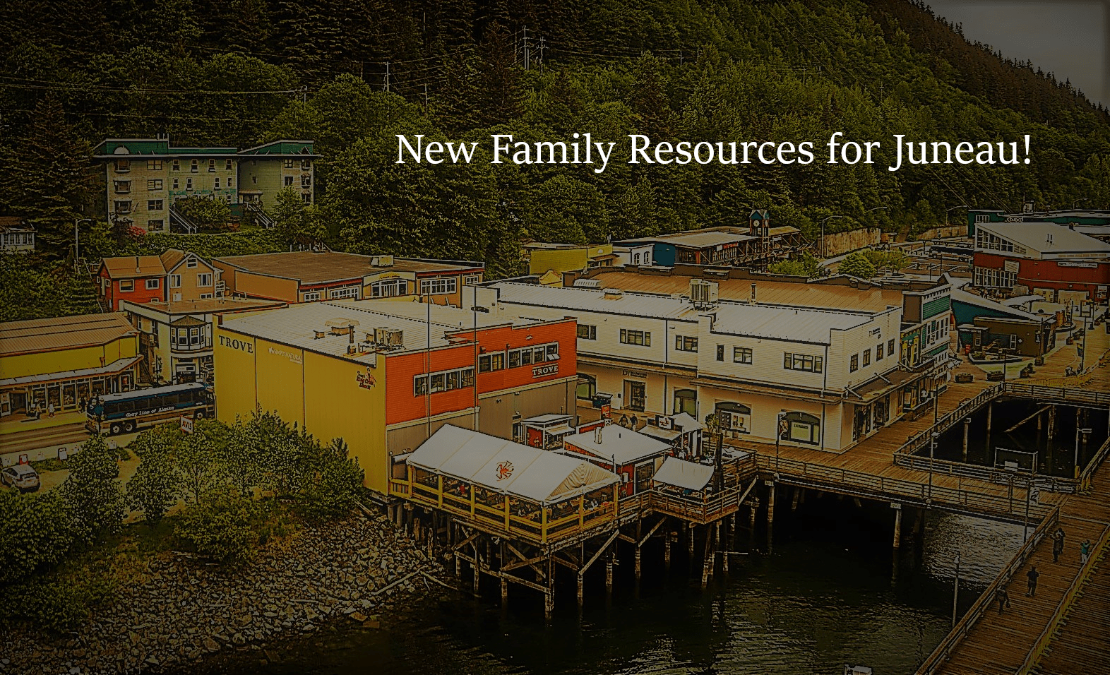 New Family Resources for Juneau is in bold white text at the top of an image of Juneau, Alaska's waterfront near South Franklin Street