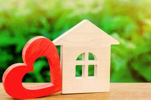 A wooden house silhouette and a red-stained wooden heart are in the foreground. Green foliage makes up the background.